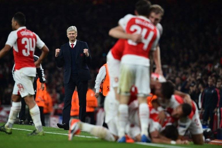 Arsenal's French manager Arsene Wenger (2L) reacts as his players celebrate Arsenal's German midfielder Mesut Ozil goal during the UEFA Champions League football match between Arsenal and Bayern Munich at the Emirates Stadium in London, on October 20, 2015. Arsenal won the match 2-0. AFP PHOTO / BEN STANSALL / AFP PHOTO / BEN STANSALL