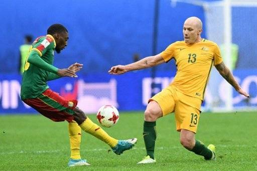 Cameroon's forward Karl Toko Ekambi (L) vies for the ball against Australia's midfielder Aaron Mooy during the 2017 Confederations Cup group B football match between Cameroon and Australia at the Saint Petersburg Stadium on June 22, 2017. / AFP PHOTO / Kirill KUDRYAVTSEV